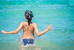 O menino caucasiano novo salta na água, mar Mediterrâneo foto de stock