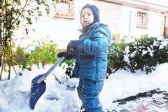 O menino caucasiano pequeno trabalha com pá a neve na jarda com os arbustos cor-de-rosa nevados bonitos Criança com jogos da pá f fotografia de stock