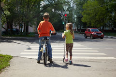 O menino com bicicleta e sua irmã com 'trotinette' estão Fotografia de Stock