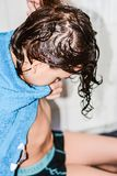 O menino com cabelo longo consegue seu cabelo cortar pelo cabeleireiro Foto de Stock Royalty Free