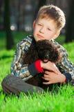 O menino com caniche preta Fotografia de Stock