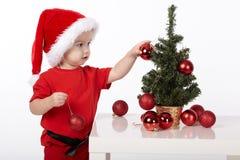 O menino com chapéu de Santa decora a árvore de Natal Imagem de Stock
