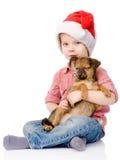 O menino com chapéu de Santa está guardando um cachorrinho Isolado no branco Imagens de Stock