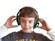 O menino com fones de ouvido escuta a música no fundo branco foto de stock royalty free