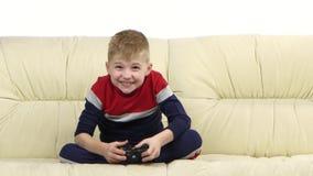 O menino com jogos consola o jogo do jogo de vídeo no sofá video estoque