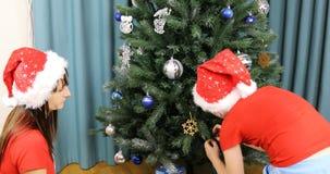O menino com a mamã em tampões do Natal decora a árvore do ano novo filme