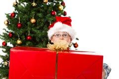 O menino com o presente grande do Natal e os olhos abrem largamente Imagens de Stock Royalty Free