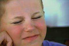 O menino com o seu eyes fechado e a demonstração do estado emocional desagradável Imagem de Stock Royalty Free