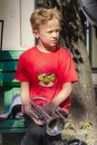 O menino com trombeta está sentando-se no banco na rua Imagens de Stock