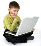 O menino com um computador Foto de Stock Royalty Free