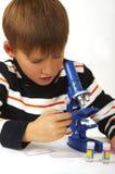 O menino com um microscópio Fotos de Stock Royalty Free