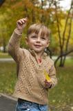 O menino com uma folha amarela de uma árvore Foto de Stock