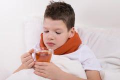 O menino com uma garganta inflamada, é tratado com o chá morno imagem de stock