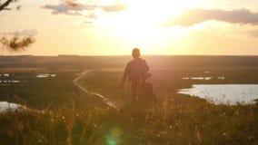 O menino com uma guitarra em um casaco azul entra no horizonte do por do sol video estoque