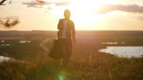 O menino com uma guitarra em um casaco azul vai do por do sol video estoque