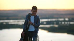 O menino com uma guitarra em um casaco azul vai do por do sol filme
