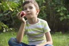 O menino com uma maçã, senta-se na grama Imagem de Stock Royalty Free