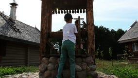 O menino com uma menina retira uma cubeta da água do bem dentro a vila do russo vídeos de arquivo