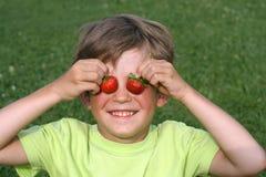 O menino com uma morango Imagens de Stock