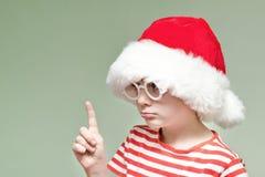 O menino com vidros e um chapéu de Santa está ameaçando com seu dedo Retrato Fotos de Stock Royalty Free