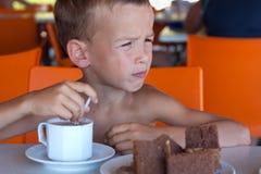O menino come em um café. Imagem de Stock