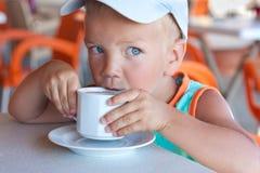 O menino come em um café. Foto de Stock Royalty Free