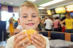 O menino come o Hamburger Imagens de Stock Royalty Free