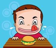 O menino come o hamburguer Fotos de Stock Royalty Free