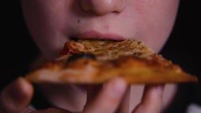 O menino come a pizza com queijo e vegetais Produtos orgânicos video estoque