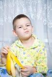 O menino come uma banana Fotografia de Stock