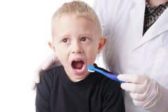 O menino consegue a ajuda pelo dentista escovar seus dentes imagem de stock