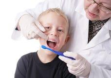 O menino consegue a ajuda pelo dentista escovar seus dentes fotos de stock