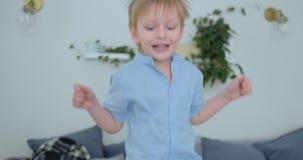 O menino considerável com cabelo branco e a camisa azul está saltando no sofá e está olhando a câmera no movimento lento