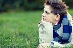 O menino considerável do adolescente encontra-se na grama e pensa-se Fotografia de Stock Royalty Free