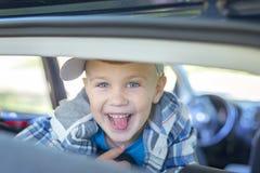 O menino considerável pequeno mostra sua língua e sorri foto de stock