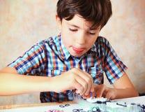 O menino considerável do Preteen faz brinquedos feitos à mão do rainbo do elástico Imagem de Stock Royalty Free