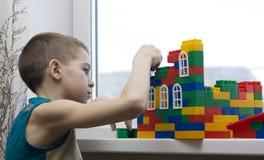 O menino constrói uma casa. Imagens de Stock Royalty Free