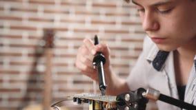 O menino constrói uma placa de circuito eletrônica do modelo e das soldas do robô com ferro de solda filme