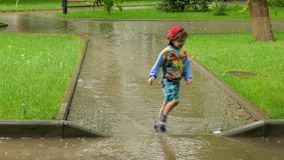 O menino corre através da poça na chuva video estoque