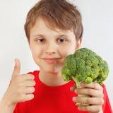 O menino cortado novo em uma camisa vermelha recomenda brócolis no fundo branco fotografia de stock royalty free