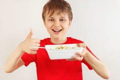 O menino cortado novo em uma camisa vermelha recomenda macarronetes imediatos no fundo branco imagem de stock