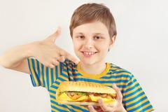 O menino cortado novo recomenda o cheeseburger no fundo branco imagem de stock royalty free