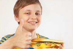 O menino cortado novo recomenda e gosta do cheeseburger grande no fundo branco foto de stock royalty free