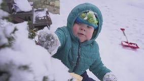 O menino a criança encontra-se na neve perto da árvore de Natal e é jogado com as decorações exteriores vídeos de arquivo