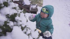 O menino a criança encontra-se na neve perto da árvore de Natal e é jogado com as decorações exteriores video estoque