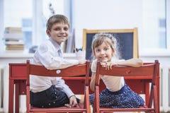 O menino, crianças da menina na escola tem um feliz, curioso, esperto Foto de Stock