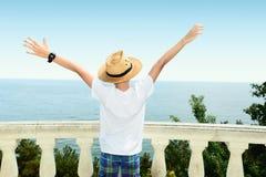 O menino custa na perspectiva do mar e de usar a tabuleta Fotografia de Stock