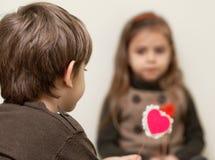 O menino dá o coração à menina Imagens de Stock