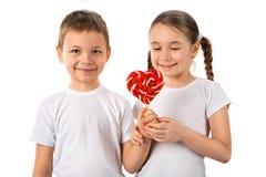 O menino dá a uma menina o coração do pirulito dos doces isolado no branco Dia do `s do Valentim Amor das crianças Foto de Stock