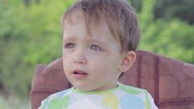 O menino da criança bebe a água de um vidro filme